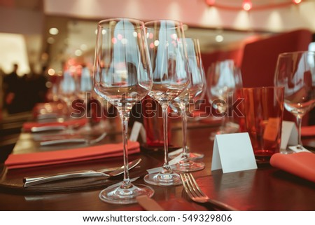 wine glass setup on the dinner table in luxury dinner party, Blurry background with vintage color style.