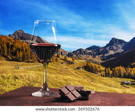Wine glass with chocolate and beautiful autumn mountainscape - stock photo