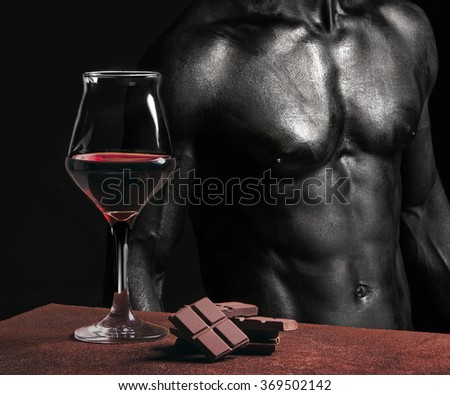 Wine glass with chocolate and male chest painted in black - stock photo