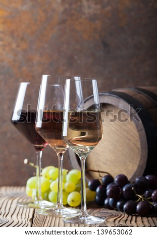 Wine glass with grapes and barrel. Red, white and rose - stock photo