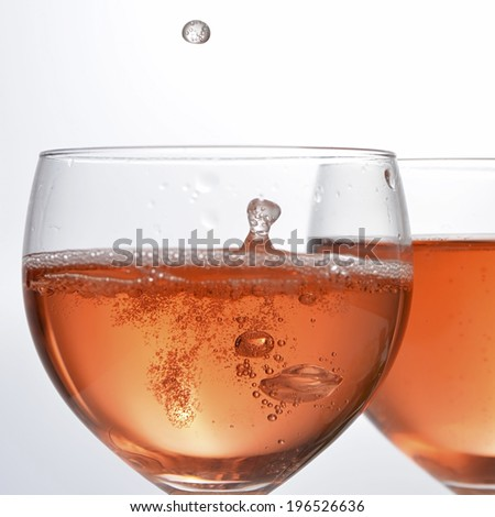 wine glass with red sparkling drink and drops - stock photo