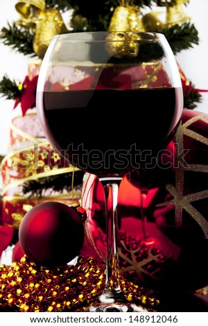 wine glass with red wine and Christmas decoration against white background  - stock photo