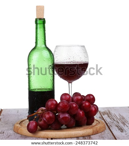 wine glass with red wine, bottle of wine and grapes on board isolated over white background - stock photo