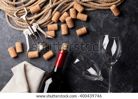 Wine, glasses and corkscrew over stone background. Top view - stock photo