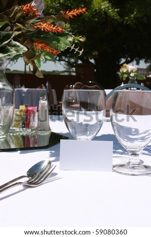 wine glasses and silverware on outdoor reception - stock photo