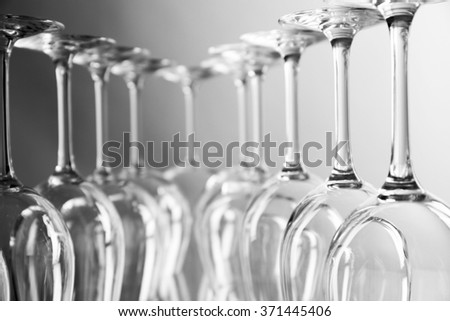 Wine glasses in a row upside down on light grey background - stock photo