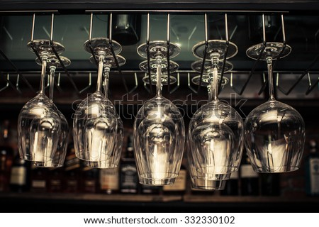 wine glasses in shelf above a bar rack in restaurant - stock photo