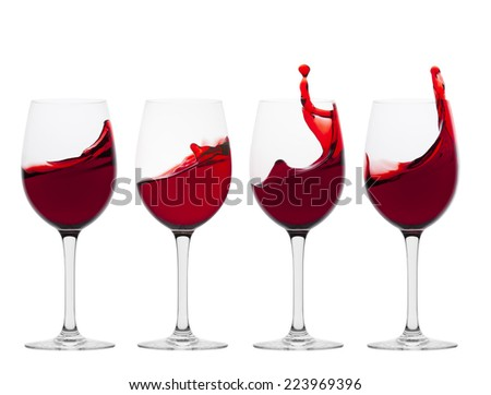 Wine glasses in toasting gesture with splash isolated on white - stock photo
