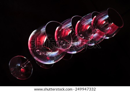 Wine glasses lit by red, blue, lilac nightclub party lights on black background