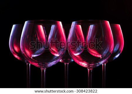 Wine glasses lit by red, blue, lilac nightclub party lights on black background  - stock photo