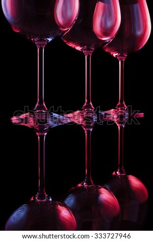 Wine glasses lit by red, blue, lilac nightclub party lights on black background, abstraction  - stock photo
