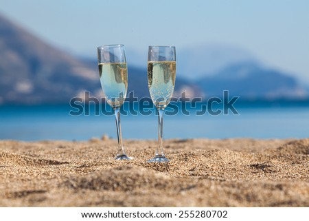 Wine glasses on a beach - stock photo
