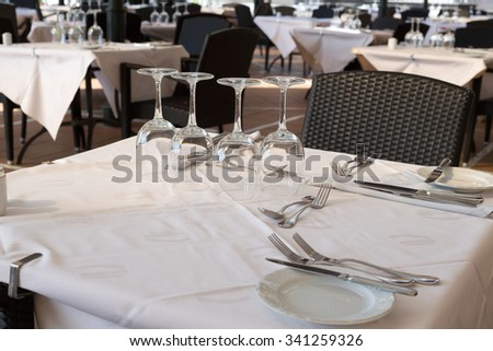 Wine glasses on a table in a restaurant. Preparing for the party. - stock photo
