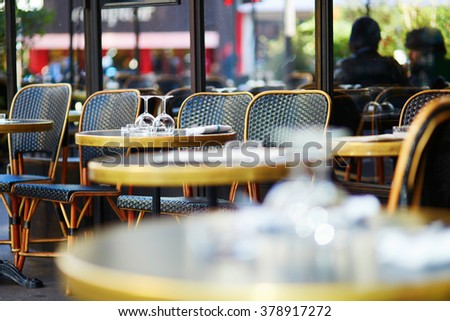 Wine glasses on a table of cozy Parisian outdoor cafe - stock photo