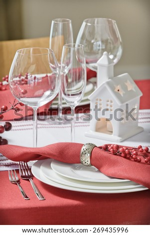 wine glasses on a table with a red tablecloth for the holiday and ceramic candlestick in the form of house - stock photo