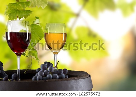 Wine glasses on wooden table with wodden barrel - stock photo
