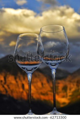 Wine glasses ready to toast while viewing an incredible sunset on Ajax and Telluride peak in Telluride Colorado. - stock photo