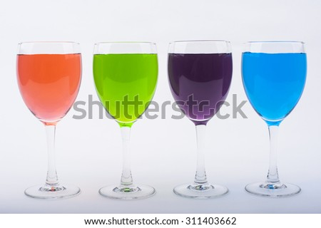 Wine Glasses with Brightly Colored Water on a White Background - Purple, Pink, Light Green, Light Blue