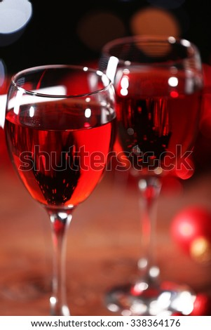 Wine glasses with Christmas decorations on wooden table, close up
