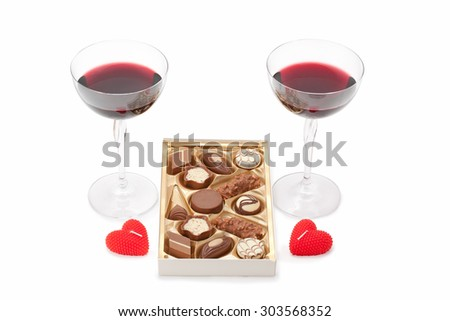 wine glasses with wine, chocolate and candles isolated on white background - stock photo