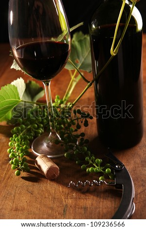 Wine goblet, bottle and cork on the wooden surface - stock photo