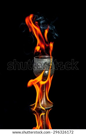 Wine goblet with Fire flames on black background - stock photo