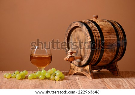 Wine in a glass grapes and wooden barrel on the table - stock photo