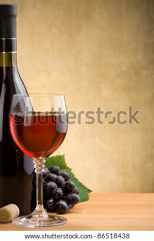 wine in glass and bottle at wood texture - stock photo