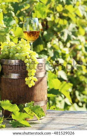Wine in glass with bunch of grape on wooden barrel