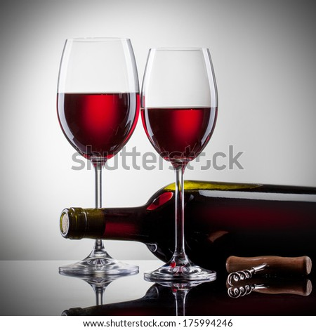 Wine in glasses and bottle on white