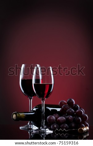 Wine in glasses with grape and bottle on red - stock photo