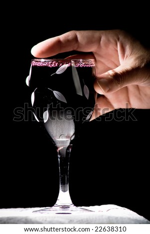 wine in hand, black background