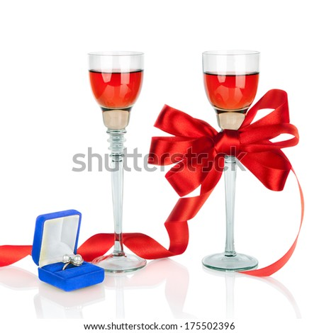 Wine in two wineglasses with red satin  bow and wedding rings in blue gift box isolated on white background  - stock photo
