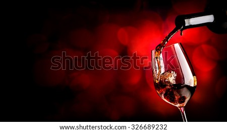 Wine pouring in wineglass on the vinous background - stock photo