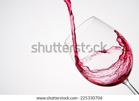 Wine pouring into a glass in diagonal composition and white background - stock photo