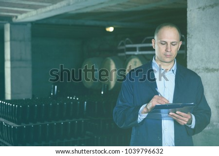 Wine producer with clipboard inspecting wine bottles on racks in wine cellar
