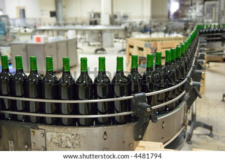 Wine production line - unlabeled bottles - stock photo