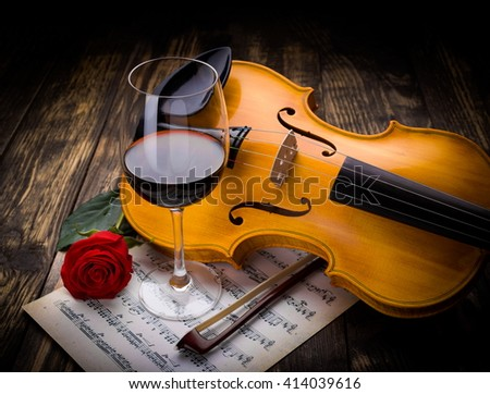 Wine, rose, musical sheet and violin on dark wood - stock photo