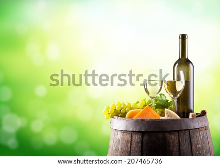 Wine still life on wooden keg with blur green abstract background - stock photo