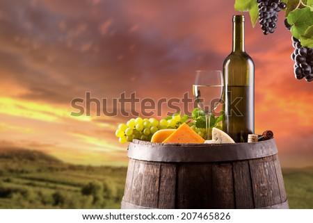 Wine still life on wooden keg with vineyard on background - stock photo