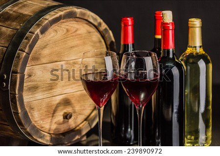 Wine still life with red wine by the glass and barrel - stock photo