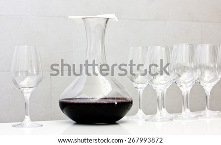 Wine tasting: a decanter of red wine covered by a napkin and a row of glasses - stock photo
