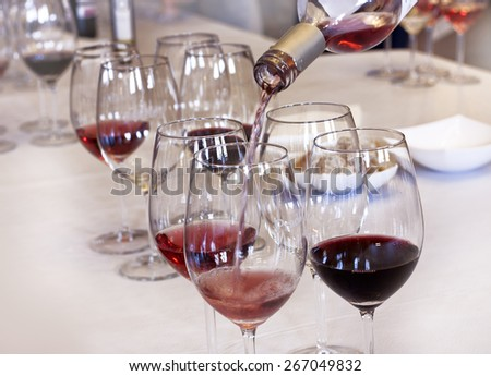 Wine tasting: rose wine being poured into a glass - stock photo