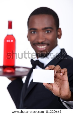Wine waiter holding forth a business card left blank for your details - stock photo