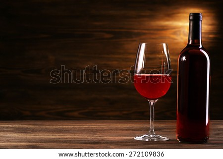 Wineglass and bottle on wooden background - stock photo