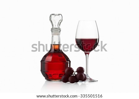 Wineglass, carafe of wine and red grapes isolated on white background - stock photo