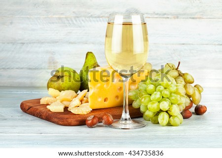 Wineglass white wine with fruits nut and cheese Parmesan still life on vintage wooden board - stock photo
