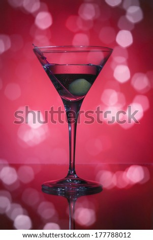 wineglass with martini and olives on red background.