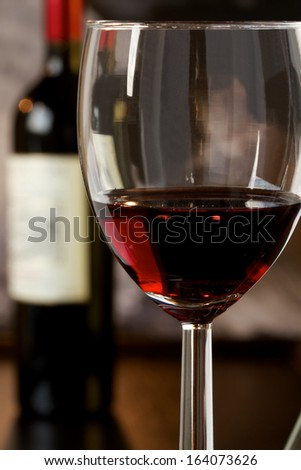 Wineglass with red wine and a bottle in the background - stock photo