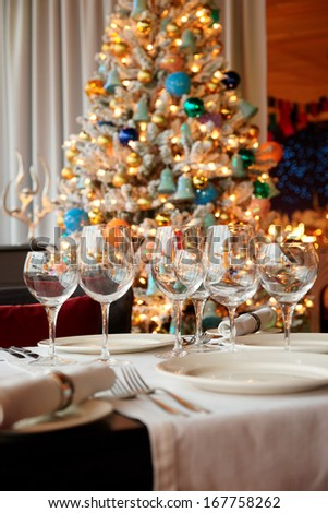 Wineglasses and Christmas tree in background, shallow focus